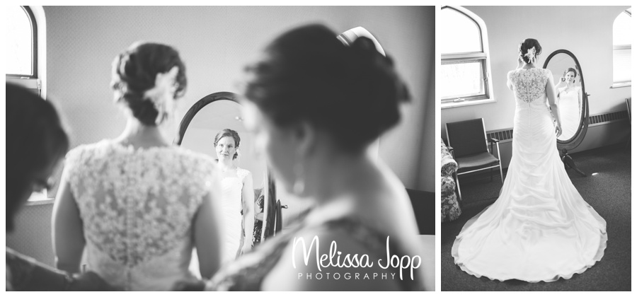 bride looking at herself in mirror at church mn wedding photographer